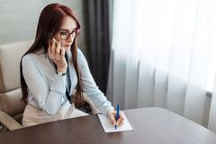 Rödhårig kvinnlig formgivare som noterar detaljer av arbete under telefonkonversation royaltyfri bild