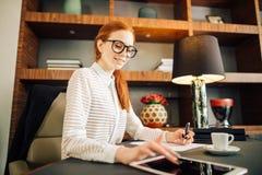 Rödhårig man som ler den unga kvinnliga chefen som använder den moderna digitala minnestavlan på kontoret Royaltyfri Foto
