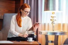 Rödhårig man som ler den unga kvinnliga chefen som använder den moderna digitala minnestavlan på kontoret Arkivfoton