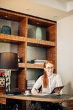 Rödhårig man som ler den unga kvinnliga chefen som använder den moderna digitala minnestavlan på kontoret Arkivbild