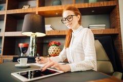 Rödhårig man som ler den unga kvinnliga chefen som använder den moderna digitala minnestavlan på kontoret Fotografering för Bildbyråer