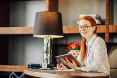 Rödhårig man som ler den unga kvinnliga chefen som använder den moderna digitala minnestavlan på kontoret Royaltyfria Bilder