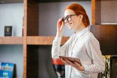 Rödhårig man som ler den unga kvinnliga chefen som använder den moderna digitala minnestavlan på kontoret Royaltyfria Foton
