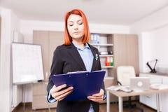 Rödhårig manaffärskvinna som rymmer en mapp med diagram och diagram Arkivfoto