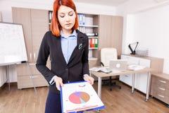 Rödhårig manaffärskvinna som rymmer en mapp med diagram och diagram Royaltyfri Fotografi