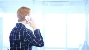 Rödhårig manaffärsman Talking på telefonen som ser till och med fönster, baksidasikt Royaltyfri Fotografi