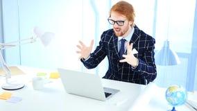 Rödhårig manaffärsman Upset vid förlust, medan arbeta på bärbara datorn, idérik formgivare Arkivfoton