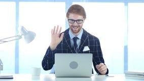 Rödhårig manaffärsmanBusy Online Video pratstund på bärbara datorn på arbete Arkivfoton