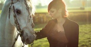 Rödhårig mandam med den vita hästen Arkivfoton