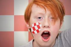 Rödhårig manfanpojken med den abstrakta flaggan målade på hans framsida Royaltyfri Fotografi