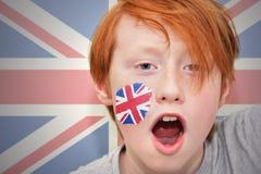 Rödhårig manfanpojken med den brittiska flaggan målade på hans framsida Arkivbilder