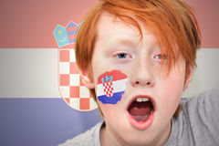 Rödhårig manfanpojken med den kroatiska flaggan målade på hans framsida Royaltyfri Bild