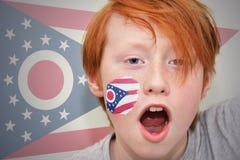 Rödhårig manfanpojken med den ohio statflaggan målade på hans framsida Arkivfoton