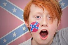 Rödhårig manfanpojken med förbundsmedlemflaggan målade på hans framsida Royaltyfria Bilder