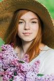 Rödhårig manflicka med en bukett av lilor i en vårträdgård Royaltyfria Bilder
