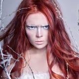 Rödhårig manflicka med långt hår, en framsida som täckas med snö med vita ögonbryn för frost, och ögonfrans i frost, en täckt trä arkivfoton