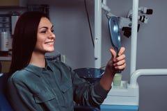 Rödhårig manflicka som sitter i en tandläkarestol med spegeln i händer som ser henne arkivbild