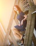 Rödhårig manflickasammanträde på gammal trätrappa Royaltyfri Foto