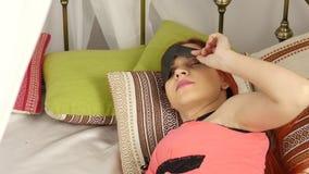 Rödhårig mankvinna i en maskering för att sova som sover i säng på en kulör kudde i en dag lager videofilmer