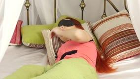 Rödhårig mankvinna i en maskering för att sova som sover i säng på en kulör kudde i en dag arkivfilmer
