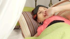 Rödhårig mankvinna i en maskering för att sova som sover i säng på en kulör kudde i en dag