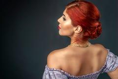 Rödhårig mankvinna med den eleganta flätade frisyren som isoleras över grå färger Royaltyfri Fotografi