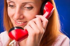 Rödhårig mankvinna med den röda telefonen Arkivfoton