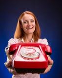 Rödhårig mankvinna med den röda telefonen Royaltyfria Bilder