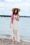 Rödhårig mankvinna med sugrörhatten på stranden Arkivfoton