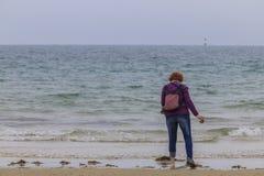 Rödhårig mankvinna på kusten arkivbilder