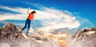 Rödhårig mankvinna som ner faller mellan kullar på klippan arkivfoto