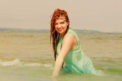 Rödhårig mankvinna som poserar i vatten under sommartid Royaltyfria Foton