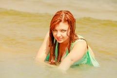 Rödhårig mankvinna som poserar i vatten under sommartid Royaltyfri Foto