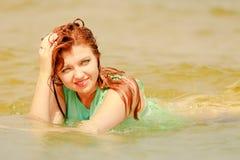 Rödhårig mankvinna som poserar i vatten under sommartid Arkivbild