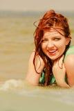 Rödhårig mankvinna som poserar i vatten under sommartid Arkivbilder