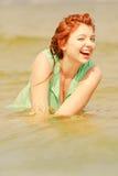 Rödhårig mankvinna som poserar i vatten under sommartid Arkivfoto