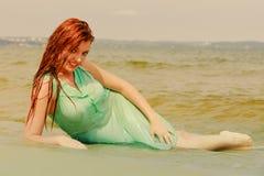 Rödhårig mankvinna som poserar i vatten under sommartid Fotografering för Bildbyråer