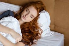 Rödhårig mankvinna som sover i sängen royaltyfri fotografi
