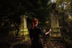Rödhårig mankvinna som utför ritual på graven arkivfoton