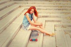 Rödhårig mankvinnor som sitter på gatatrappa, hör hennes skridsko stiga ombord Royaltyfria Bilder