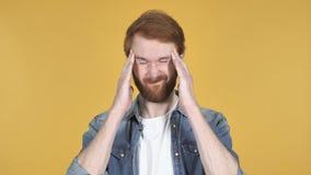 Rödhårig manman med huvudvärken, gul bakgrund arkivfilmer