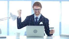 Rödhårig manman som är upphetsad för den lyckade online-transaktionen, betalning vid kreditkorten Royaltyfri Fotografi