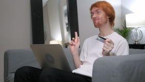 Rödhårig manman som är upphetsad för lyckad online-shopping stock video