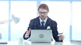 Rödhårig manman som reagerar för att missa online-transaktionen, betalning vid kreditkorten Arkivfoto