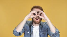 Rödhårig manman som söker med handgjord kikare, gul bakgrund stock video