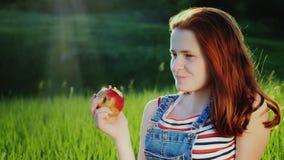 Rödhårig tonåring som äter ett saftigt rött äpple på en picknick Ett pittoreskt ställe - en grön äng, härlig ilsken blick från lager videofilmer
