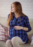 Rödhårig ung gravid kvinna som hemma sitter på soffan och arkivbild