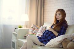 Rödhårig ung gravid kvinna som hemma sitter på soffan och royaltyfri foto