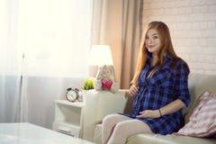 Rödhårig ung gravid kvinna som hemma sitter på soffan och arkivfoton