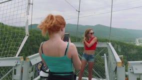 Rödhåriga mannen för två unga kvinnor och blont tar bilder av de mot bakgrunden av den gröna bergdalen från över stock video